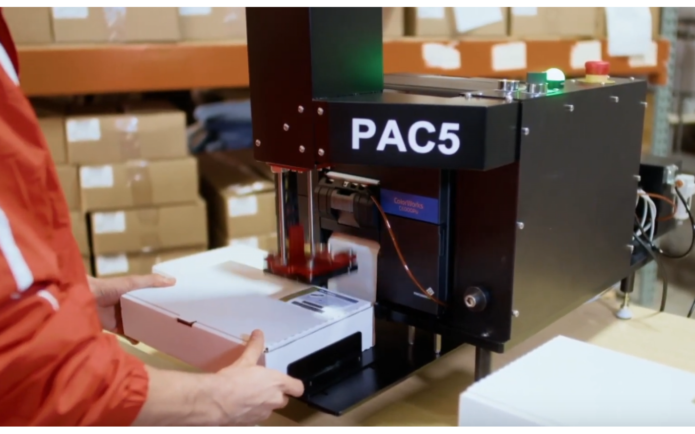 worker applying cannabis label to product using PAC5 label applicator